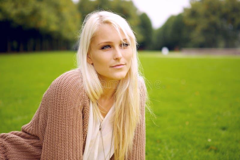Fridsam kvinna som sitter i en park fotografering för bildbyråer