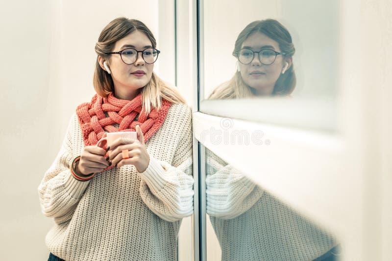Fridsam långhårig flicka i trådlös hörlurar som ser utanför fönstret fotografering för bildbyråer