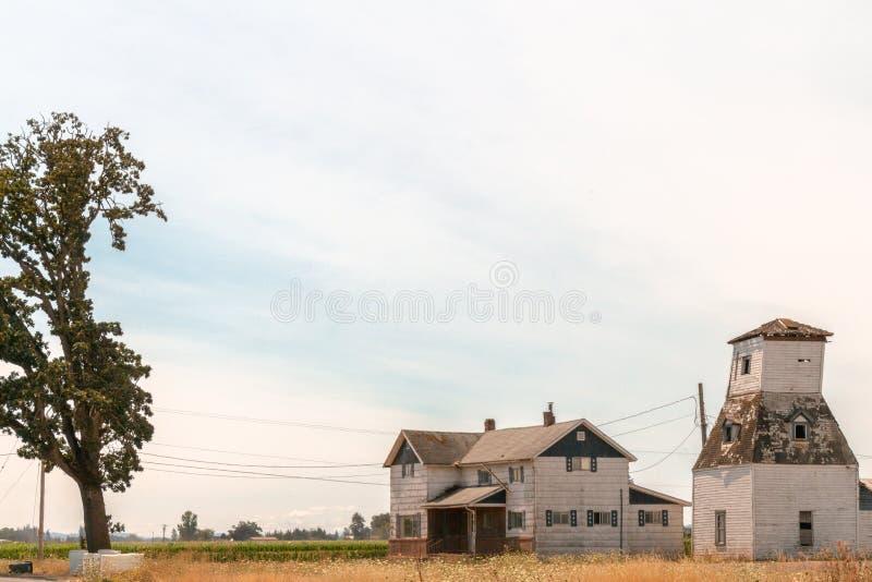 Fridsam liten lantgård i ett fält på bygden royaltyfri bild