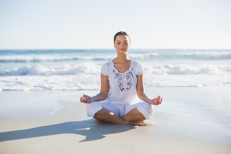 Fridsam nätt kvinna i lotusblommaposition på stranden royaltyfria bilder