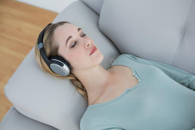 Fridsam naturlig kvinna som lyssnar till musik, medan ligga på soffan arkivbilder