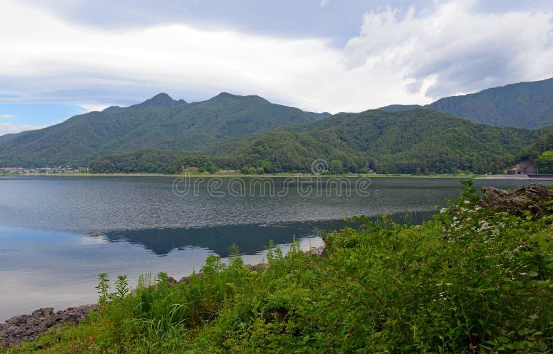 Fridsam naturplats med gröna berg, träd och sjön i Kawaguchiko nära Mount Fuji royaltyfri fotografi