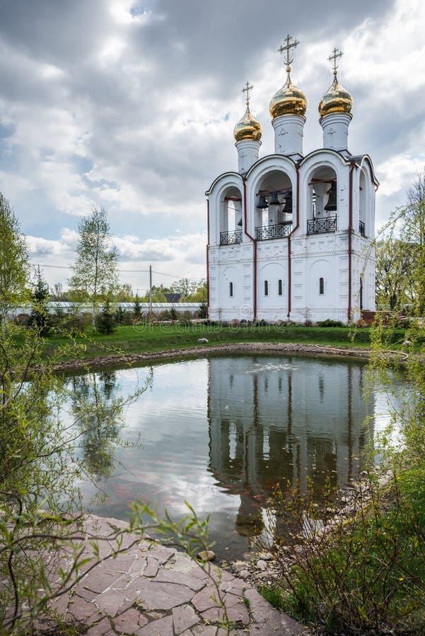 Fridsam och tyst sikt av klockstapeln, reflekterad i en sjö royaltyfria foton