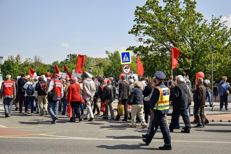 Fridsam procession av folk med röda flaggor och ballonger på den huvudsakliga gatan royaltyfria bilder