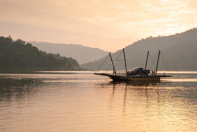 Fridsam sikt, turister och medel på den lokala bilfärjan i Sirikit sjön, Nan Province, Thailand Resande på solnedgångtid Sommar arkivbild