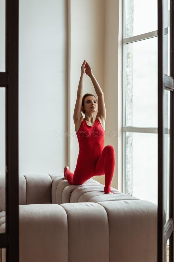 Fridsam snygg kvinna som står på hennes knä, medan göra yoga arkivfoto