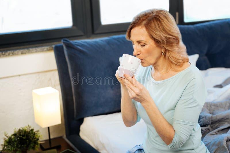 Fridsam snygg ljus-haired kvinna som läppjar den varma drinken arkivbild