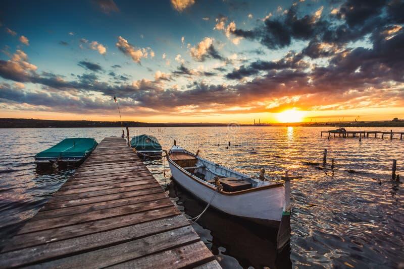 Fridsam solnedgång med dramatiska himmel och fartyg och en brygga royaltyfri foto