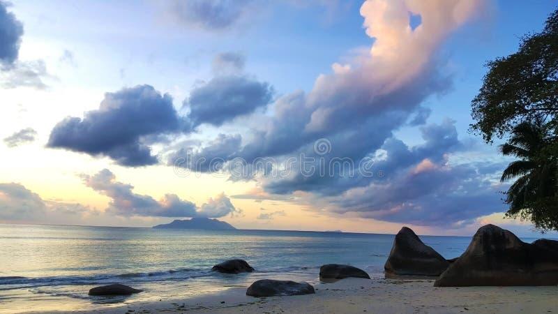 Fridsamma Seychellerna sätter på land solnedgång med att förbluffa himmel och vaggar royaltyfri bild