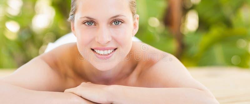 Fridsamt blont ligga på handduken som ler på kameran arkivfoton