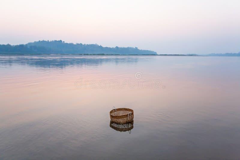 Fridsamt fridfullt vid floden, en bambukorg doppar i Mekonget River på vintermorgonen, stilleben i lantliga Laos arkivfoto