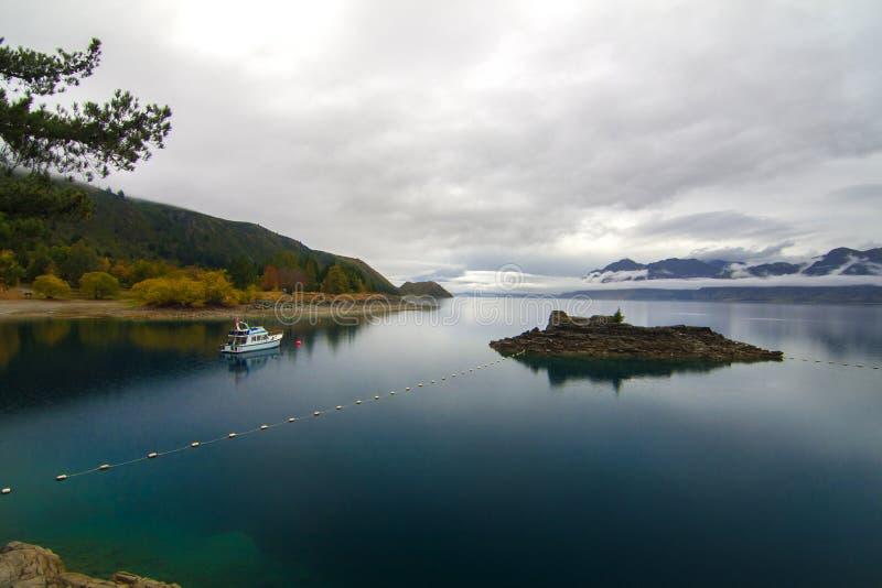 Fridsamt höstlandskap, ren djupblå sjö med vattenreflexion och feriefartyg, Otago kullar, nyazeeländsk sjö Hawea för land royaltyfri bild