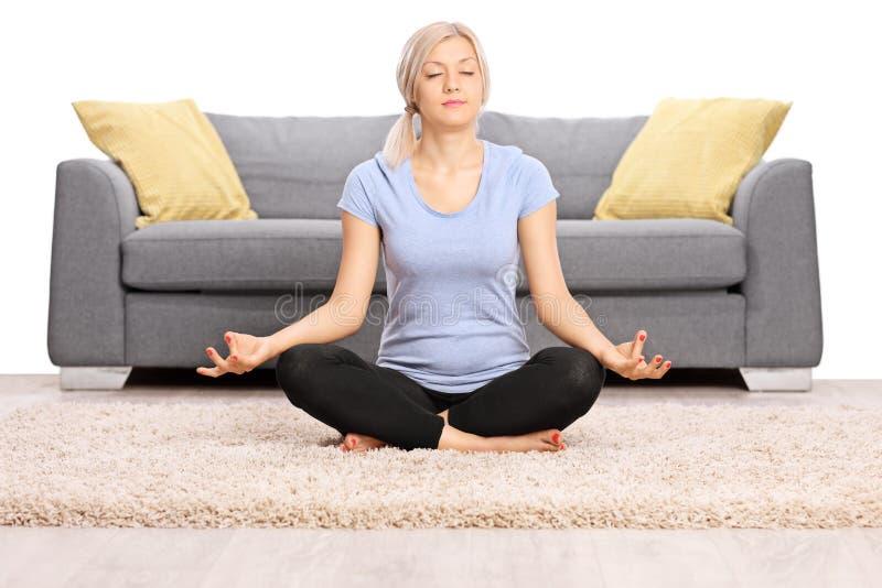 Fridsamt meditera för kvinna som placeras på golvet arkivbilder