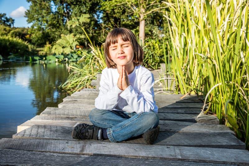 Fridsamt ungt yogabarn som tycker om att koppla av som mediterar nära vatten fotografering för bildbyråer