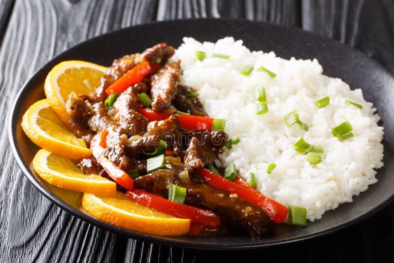 Fried Asian-Rindfleischsteak mit Gemüsepaprika in der orange Soße der Sojabohne diente mit Reisnahaufnahme auf einer Platte horiz stockfoto