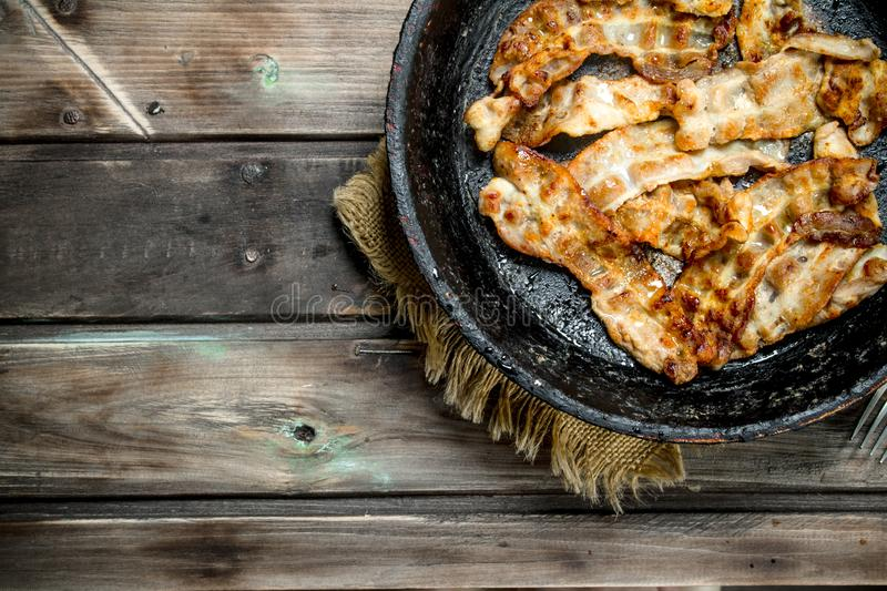 Fried bacon in a pan. On a wooden background stock images