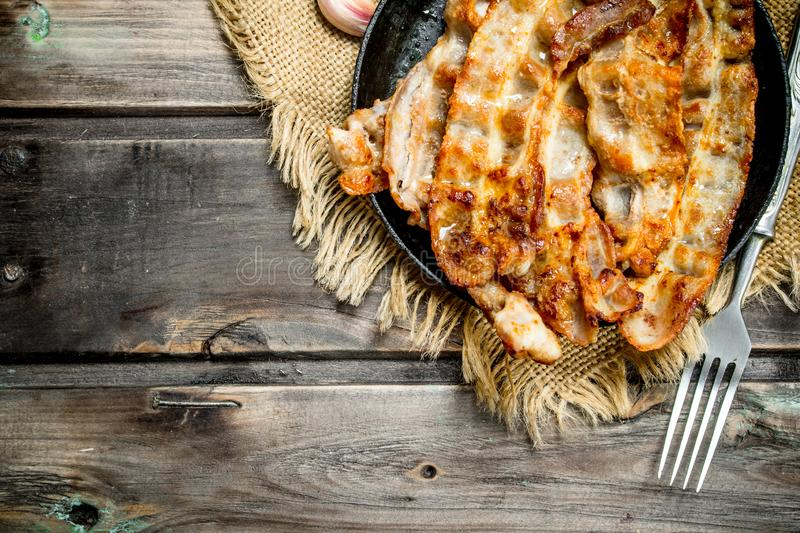 Fried bacon in a pan. On a wooden background royalty free stock image