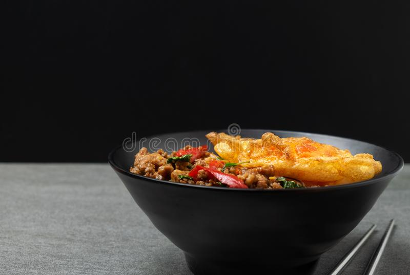Fried basil pork with fried egg and white rice in black bowl on the concrete table royalty free stock images