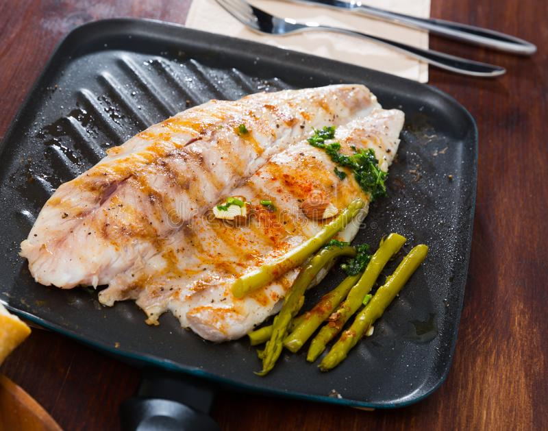 Fried bass with asparagus on the baking sheet stock image