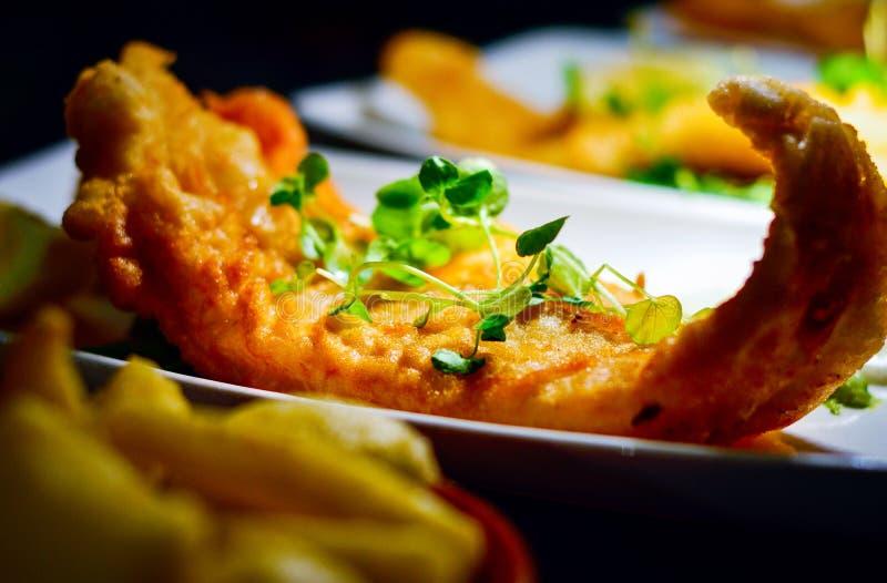 Fried Battered Fish Fillet profundo británico con las hierbas verdes imagenes de archivo