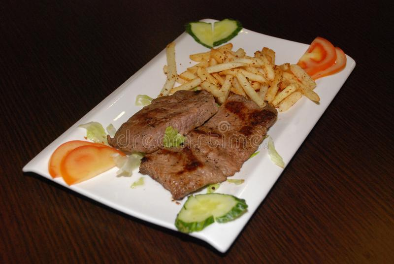 Fried beef fillet with french fries and fresh vegetables on the white plate stock photography