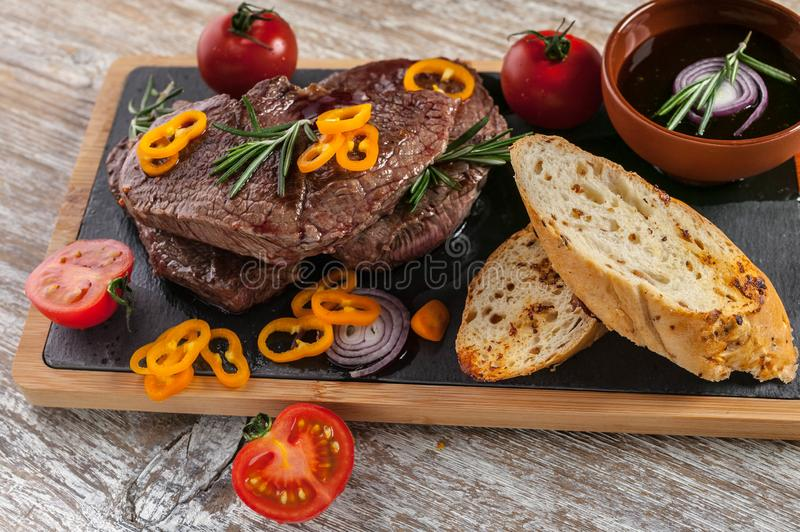 Fried Black Angus beef meat on a cutting board. Meat, spices, vegetables, croutons and rosemary royalty free stock photos
