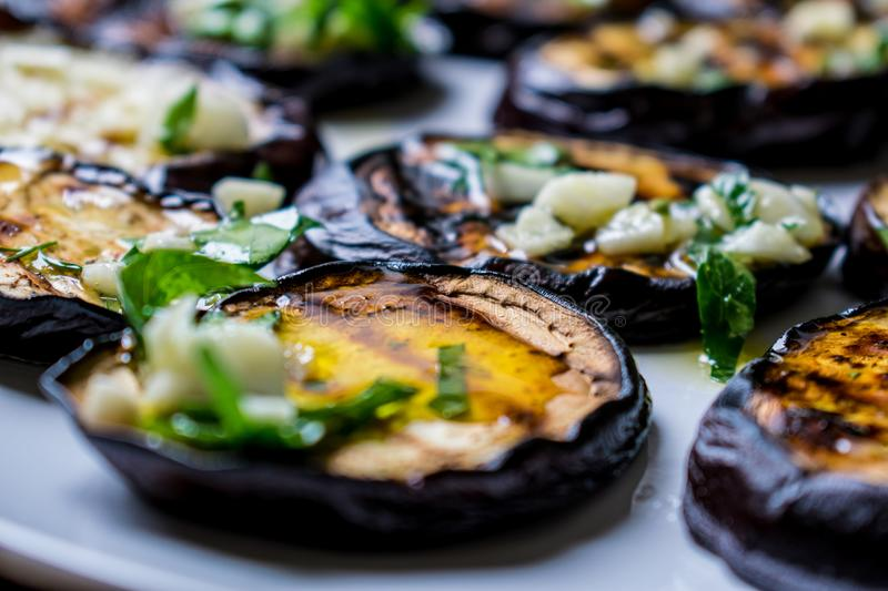 Fried blue eggplants with fresh garlic and greens on a round white plate, hot and appetizing. Homemade cooking. Delicious Grilled Food stock photo