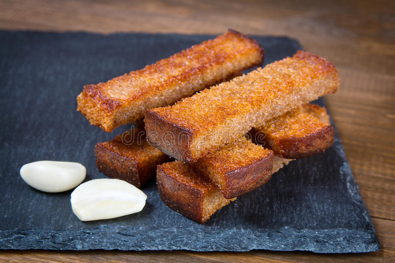 Fried bread croutons toasts and garlic. On a black stone board stock photos