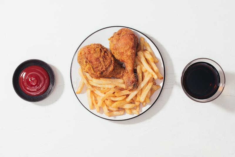 Fried breaded crispy chicken nuggets with French fries on wooden plate, ketchup and soft drink on the side stock image