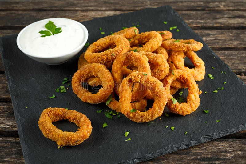 Fried Breaded Onion Rings mit Soße auf Steinbrett stockfotos