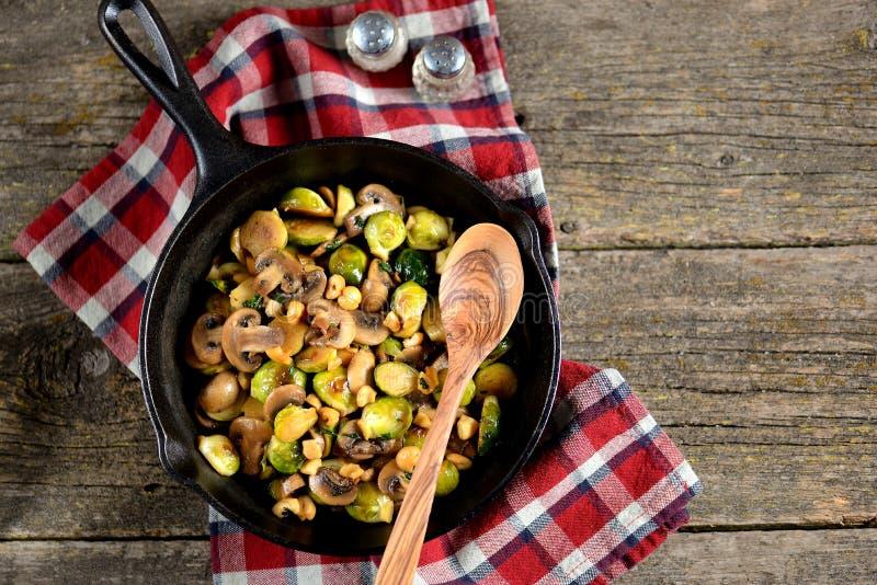 Fried Brussels brota com cogumelos e porcas em uma frigideira do ferro fundido em um fundo de madeira imagens de stock royalty free