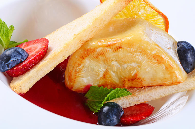 Fried camembert with berry sauce stock photography