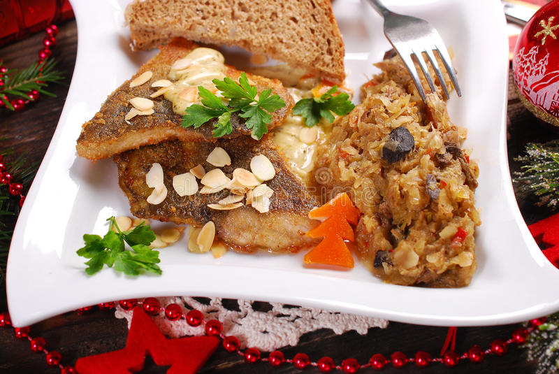 Fried carp with almonds and sauerkraut for christmas eve stock photos