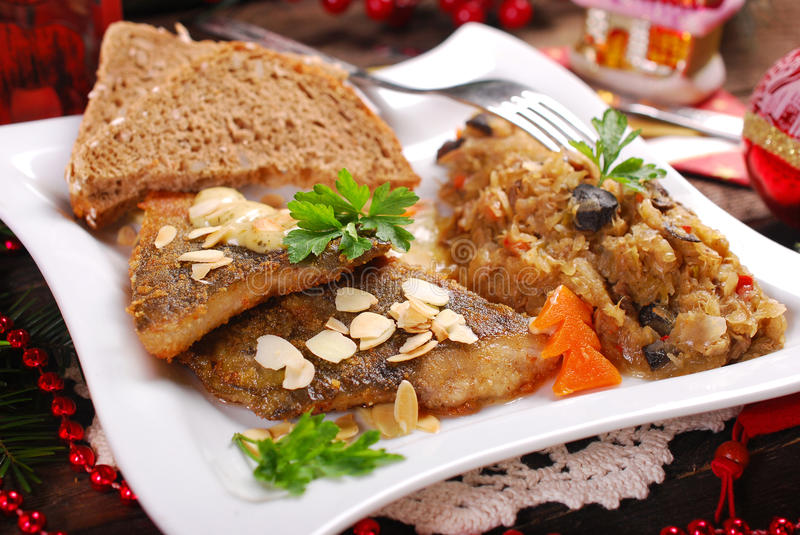 Fried carp with almonds and sauerkraut for christmas eve royalty free stock images