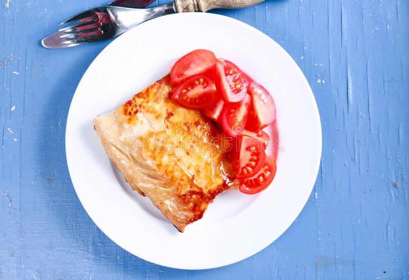 Fried carp fillet and tomatoes stock image