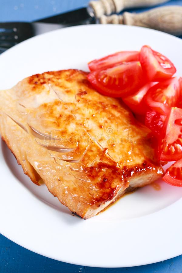 Fried carp fillet and tomatoes royalty free stock photos