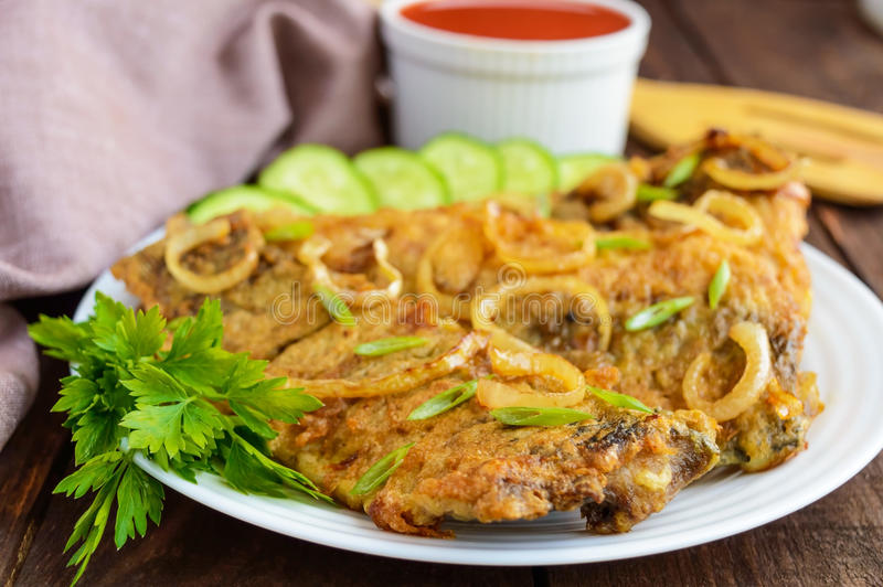 Fried carp fish fillet in batter on wooden table. stock photo