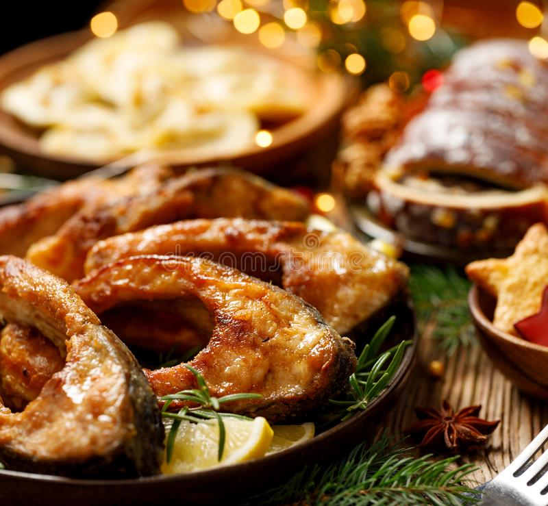 Fried carp fish slices on a ceramic plate, close up. Traditional christmas eve dish. royalty free stock photo