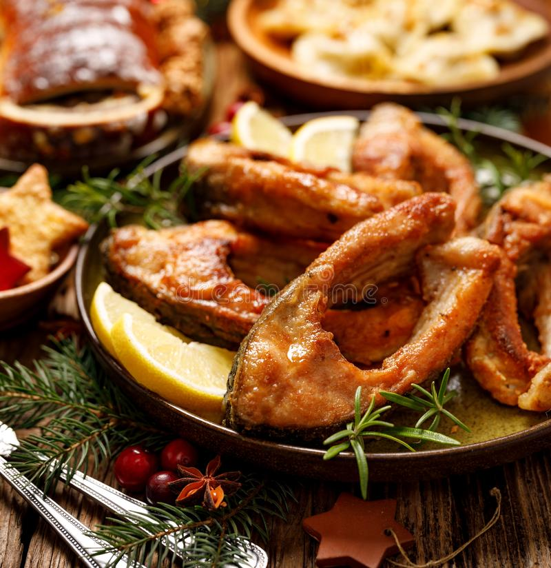 Fried carp fish slices on a ceramic plate, close up. Traditional christmas eve dish. stock photo