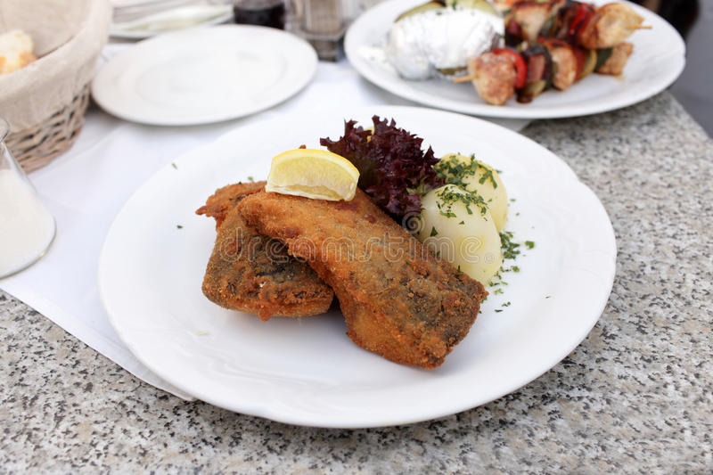 Fried carp with potatoes and slice of lemon stock images