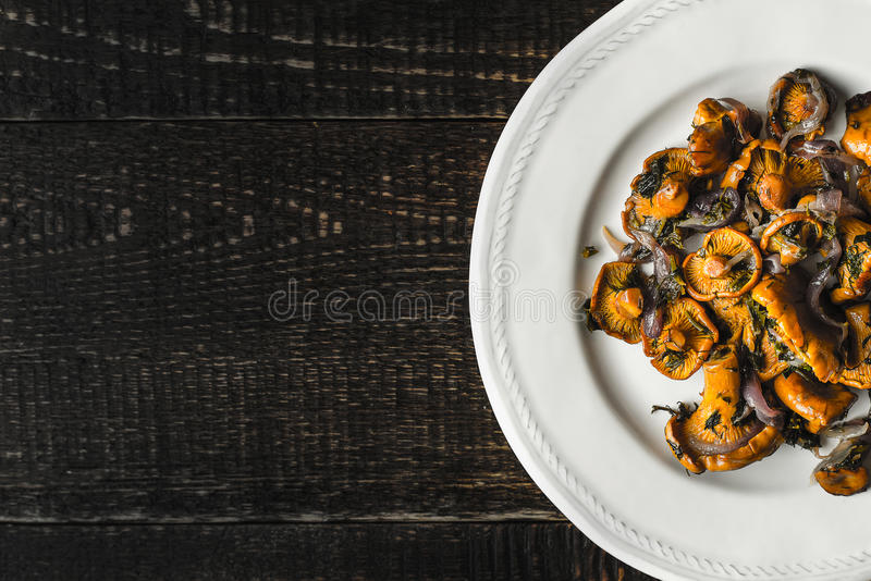 Fried chanterelles in the ceramic plate at the right of the old wooden table top view. Horizontal royalty free stock photos