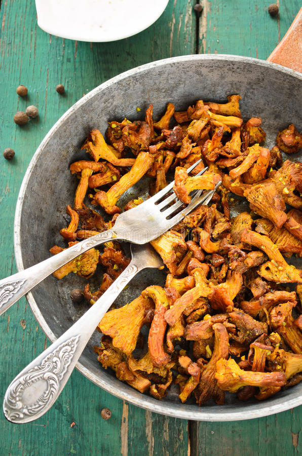 Fried Chanterelles with onions and fresh herbs in skillet. On wooden background stock image