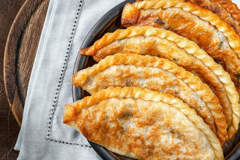 Fried chebureki on a clay plate. Close-up, top view. stock image