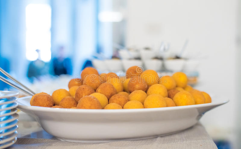 Fried Cheese Balls. A close up shot of round panned and fried cheese balls in a white deep plate on a big buffet table royalty free stock images