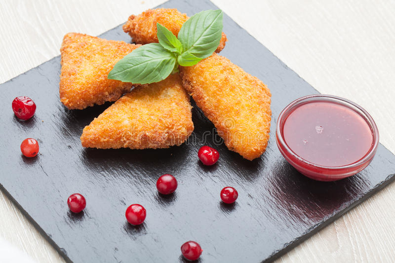 Fried cheese sticks served with cranberries, sauce on black stone royalty free stock images