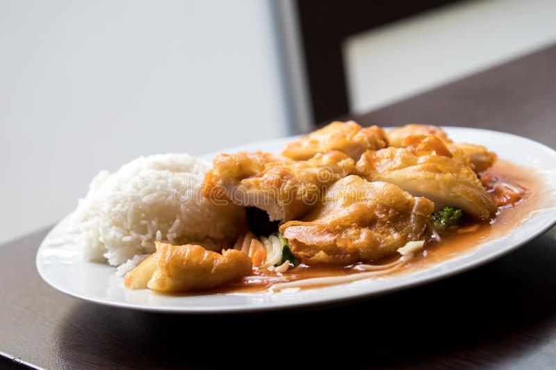 Fried chicken on Asian sweet sour sauce with rice in Asia restaurant royalty free stock images