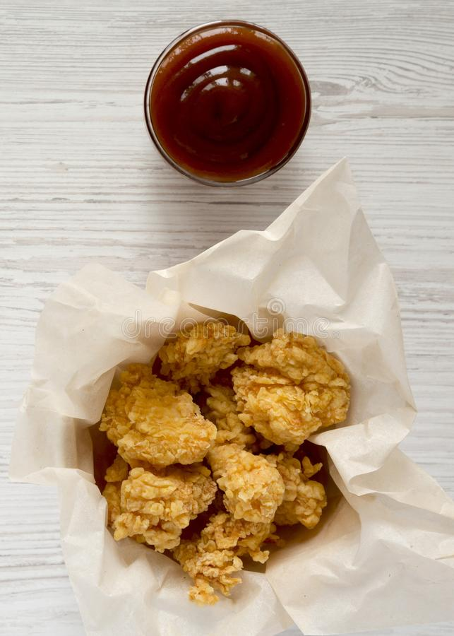 Fried chicken bites in paper box, barbecue sauce over white wooden surface, top view. Flat lay, overhead, from above. Close-up.  royalty free stock images