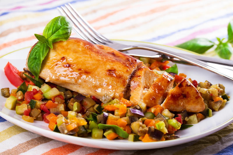 Fried chicken breast with sauteed vegetables. Eggplant, carrot, zucchini, squash and tomatoes stock photo