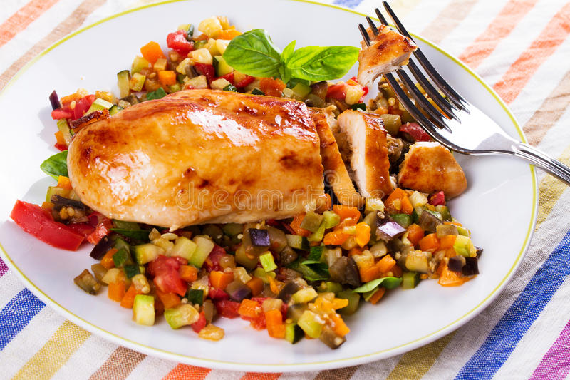 Fried chicken breast with sauteed vegetables. Eggplant, carrot, zucchini, squash and tomatoes royalty free stock photography
