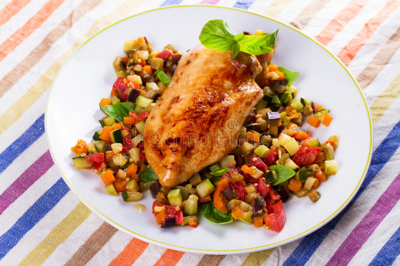 Fried chicken breast with sauteed vegetables. Eggplant, carrot, zucchini, squash and tomatoes. View from above, top studio shot royalty free stock image